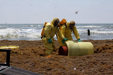 HAZMAT workers conduct a recovery of a barrel of unknown content on Galveston Island.