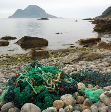 Marine litter of ropes and fishing nets washed up on beach nets,beach,coast,norge,rope,litter,environment,environmental issues,marine debris,plastic waste,marine litter,rocky beach,green rope,colourful,stones,bolders