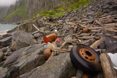 Marine debris on rocky shoreline in Troms sea,nature,trash,coast,debris,litter,coastline,environmental issues,marine debris,plastic waste,marine litter,plastic litter,strandline,wheel,driftwood,drum