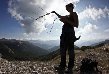 Researcher collecting field data for an Apennine brown bear project conservation,endemic,subspecies,Europe,Lazio e Molise,Parco Nazionale d'Abruzzo,large mammals project,La Sapienza University,Rome,field data collection,telemetry,radio tracking,clouds,sky,mountainside