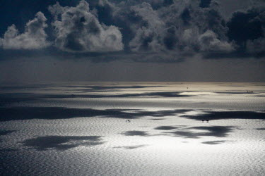 Clouds cast their shadows on the Gulf of Mexico clouds,shadows,sea,gulf,marine,seascape,oil platforms,grey,horizon
