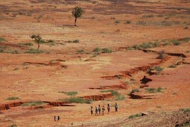People walking through the Sahel people,land,warming,desert,dry,shrubs,bushes,grasses,walking,carrying,line,dry riverbed,earth,sahel,africa