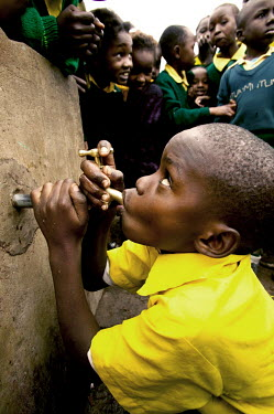 Conservation Issues: school children drinking from tap Africa,conservation,conservation issue,conservation issues,water,clean water,drinking water,collect,collecting,urban,village,people,tap,shallow focus,drink,drinking,thirst,face,hands,mouth,school chil