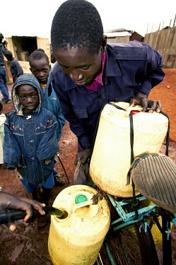 Conservation Issues: collecting water, which is in short supply Africa,conservation,conservation issue,conservation issues,water,clean water,drinking water,collect,collecting,drum,pour,pouring,urban,village,people,containers,bike,adult,child,children,locals,villag