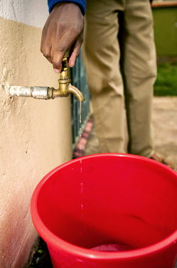 Conservation Issues: open tap illustrating low water pressure/shortage Africa,conservation,conservation issue,conservation issues,water,clean water,drinking water,collect,collecting,urban,village,people,tap,pressure,low pressure,open,drip,red,bucket,turn,hand,shallow foc