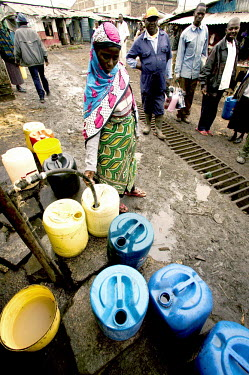 Conservation Issues: collecting water, which is in short supply Africa,conservation,conservation issue,conservation issues,water,clean water,drinking water,collect,collecting,drum,drums,pour,pouring,urban,village,people,containers,adult,adults,locals,villagers,hos