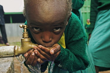 Conservation Issues: school children drinking from tap Africa,conservation,conservation issue,conservation issues,water,clean water,drinking water,collect,collecting,urban,village,people,tap,shallow focus,drink,drinking,thirst,face,eyes,close-up,close up,