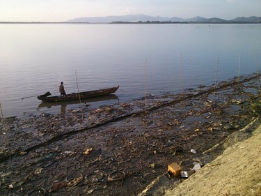 Polluted shoreline pollution,litter,plastic,environmental,rubbish,refuse,bottles,plastic bottles,carrier bags,boat,water,waterway