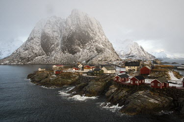 The Lofoten Islands Reine,Lofoten,Nordland,Norway,winter,Lofoten Islands,village,mountains,dramatic,mist,cloud,houses,stilts,precarious,coast,coastal,human,human settlement,rocks,rocky shore,snow,snowy,urban,house,human