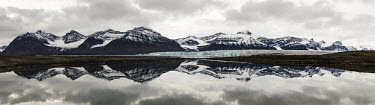 Sveabreen on Svalbard surrounded with mountains and their reflections. Svalbard,panorama,panoramic,glacier,glacial,mountains,snow,coast,water,reflection,reflections,calm,flat,clouds,Arctic,Spitsbergen,Clouds,Glacier,Mountains,Reflection