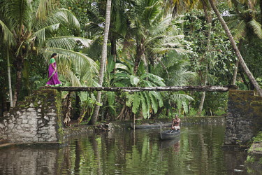 Woman with bright purple and green sari walking over a beautiful scenic canal bridge human,people,people interacting with nature,river,water,stream,natural world,boat,humans,bridge,Relaxation,On the move,Tranquility,Solitude