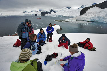 Tourists gathered around a glacierologist sharing his knowledge while gathering samples for his studies iceberg,ice,snow,cold,snowy,cold weather,winter,Christmas,freezing,frozen,landscape,habitat,climate change,global warming,climatology,climate science
