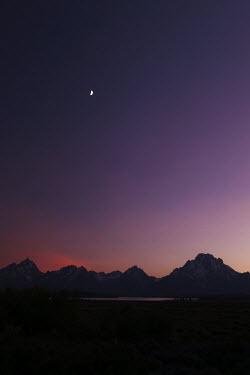 The purple sky over Grand Teton National Park landscape,moonlight,purple,pink,silhouette,shadow,night,night time,midnight,sky,night sky,mountain,mountains,Grand Teton,dusk