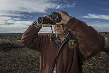 A man tracking Iberian lynx, scoping the landscape researcher,research,tracking,tracker,binoculars,looking,waiting,conservation,science,field work,lynx,Iberian lynx,humans,people
