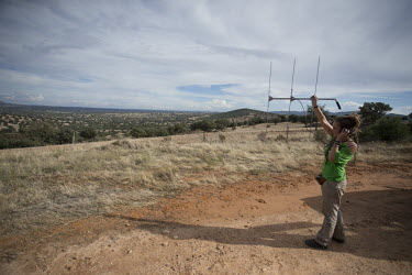 A researcher using telemetry to locate radio-collared lynx researcher,research,tracking,conservation,science,field work,lynx,Iberian lynx,humans,people,telemetry,radio tracking,antenna