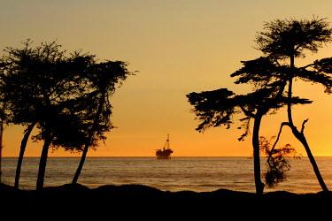 The sunset silhouette of an oil rig coast,coastal,coastline,sea,ocean,oceans,beach,sunrise,dawn,low light,silhouette,oil,oil rig,rig,natural resources,exploitation,resources,fossil fuel,fossil fuels,digging,environment,human impact,indu