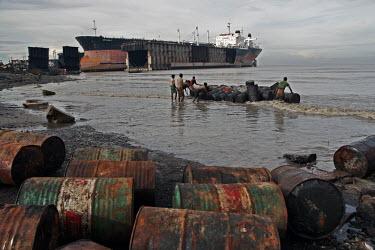 An oil tanker graveyard coast,coastal,coastline,beach,litter,trash,pollution,human impact,waste,tide,tidal,landscape,shipping,tanker,barrels,oil barrel,oil drum,oil,industry