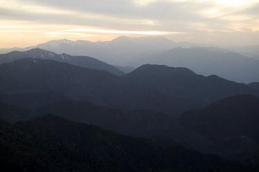 View of the high Atlas mountains ecosystem,habitat,environment,landscape,Morocco,Africa,mountains,sunset,sundown,dusk,silhouettes,hazy,mountain range,hills,altitude