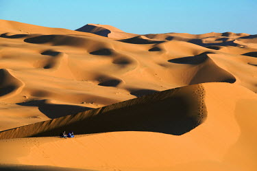 A tourist with Tuareg guide sits in the vastness of the sand dunes of the Erg Chebbi area of the Sahara desert ecosystem,habitat,environment,landscape,Morocco,Africa,sand,sand dunes,dunes,desert,shadows,shade,arid,dry,humans,people,tourist,tourism