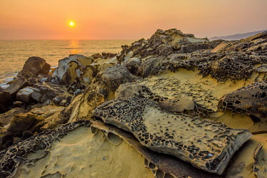 A rocky coastline at sunset Sky,environment,ecosystem,Habitat,Sea,seas,Orange background,stones,gravelly,Rock,pebble,stone,stony,rocky,gravel,pebbles,rocks,Evening,nightfall,sunsets,dusk,sun set,Sunset,Morning,Dawn,Sunset sky,Da