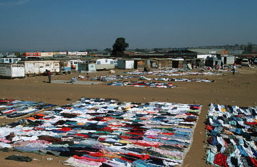 Clothes laid out for sale in informal settlement/slum area - Johannesburg, South Africa Informal settlement,Improvisation,Roofs,Rooftops,Colourful,Environment,Outside,Clothes,Sale,Market,Fabric,Subsistence