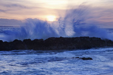 Waves crashing and spraying up against rocks - South Africa Coast,Sea,Ocean,Rocky shore,Rocks,Waves,Crashing,Spray,Sunset