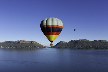 Hot air balloons rise up above a lake - South Africa Hot-air balloons,Lake,Flying,Ride,Calm,Blue sky,Clear sky,Mountains,Entertainment,Activity,Excursion,View,Colourful