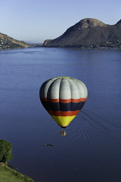 Striped hot air balloon over a lake - South Africa Hot-air balloon,Lake,Flying,Ride,Calm,Blue sky,Mountains,Entertainment,Activity,Excursion,View,Colourful