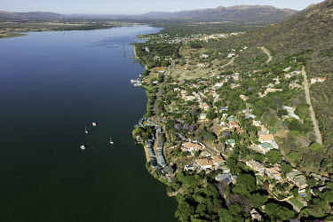View down the river with mountains in the background - South Africa Aerial,View,Up-river,Riverside,Town,Mountains,Settlement,Slope,River,Boats,Trees,Landscape