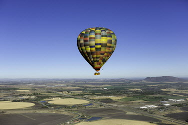 Hot air balloon rises up above farmland - South Africa Hot-air balloon,Lake,Flying,Ride,Calm,Blue sky,Clear sky,Mountains,Entertainment,Activity,Excursion,View,Colourful,High up,Farmland