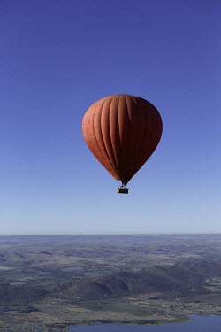 Red hot air balloon rises over mountain ranges and a lake - South Africa Hot-air balloon,Lake,Flying,Ride,Calm,Blue sky,Clear sky,Mountains,Entertainment,Activity,Excursion,View,Red