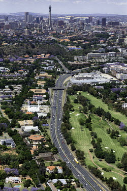Aerial view of the main highway travelling through to the city centre in the distance - Johannesburg, South Africa Aerial,Landscape,City,Suburbs,Road,Buildings,Houses,Neighbourhood,Trees,Rooftops,Settlement,Tree-lined,Colourful,Purple,Colour,City centre,Skyline,Highway,Main road,Golf course