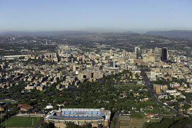 Aerial view of Johannesburg with the stadium in the foreground - Johannesburg, South Africa Aerial,Skyline,Landscape,City,City centre,Road,Clear sky,Blue sky,Highrise,Buildings,Sun,Stadium