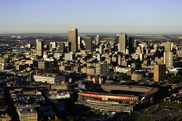 Johannesburg skyline in the sun - Johannesburg, South Africa Aerial,Skyline,Landscape,City,City centre,Road,Clear sky,Blue sky,Highrise,Buildings,Sun