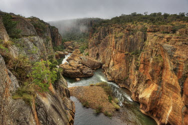 A view down a canyon with mist rising in the background - South Africa Viewpoint,View,Cliff,Canyon,Boulder,Narrow,Landscape,Formation,Mist,Adventure,River,Trees