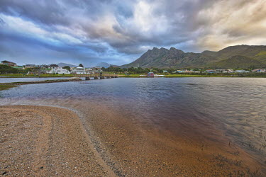 Small town of Betty's Bay under a dramatic sky - Western Cape province, South Africa Bay,Coastal,Coast,Mountain,Dramatic sky,Sky,Cloud formation,Blue,Sand,Landscape