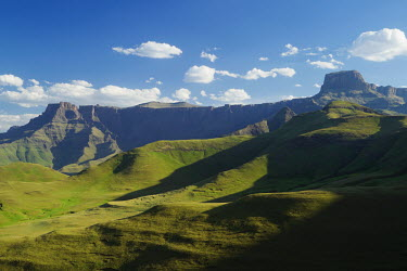 The Amphitheatre mountain formation rises straight up to the sky to over 3000 feet - South Africa Africa,African,Southern Africa,scenic,scenery,beauty in nature,natural world,non-urban scene,nature,outdoors,sky,cloud formation,blue sky,mountains,landscape,green,grass,imposing,amphitheatre