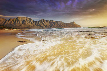 The seashore backed by the Kogelberg Mountains with dramatic clouds overhead - South Africa Beauty in nature,Stones,Pebbles,Coastal,Coast,Sea,Ocean,Sunset,Mountains,Background,Long exposure,Dramatic sky,Cloud formation,Waves,Landscape,Beach,Sand,Tranquil,Nobody