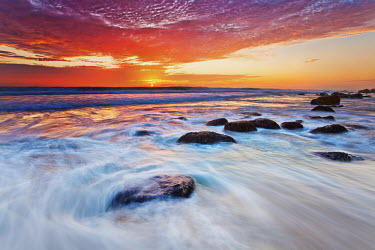 A colourful sun set over the Atlantic ocean at Betty's Bay - South Africa Beauty in nature,Sunset,Dramatic sky,Colour,Long exposure,Coast,Coastal,Waves,Rocks,Boulders,Clouds,Orange,Red,Blue