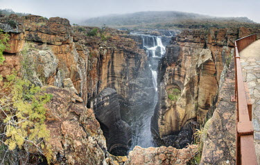 A View of a waterfall down a canyon - South Africa Viewpoint,View,Cliff,Canyon,Boulder,Narrow,Landscape,Formation,Mist,Adventure,River,Trees,Waterfall,Cascade,Powerful