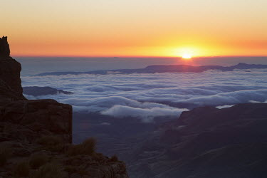 A sunset view from the Sani pass road with low clouds suspended - uKhahlamba Drakensberg Park, South Africa Sunrise,Scenic,scenery,beauty in nature,natural world,non-urban scene,nature,outdoors,Low cloud,Cloud formation,Valley,Rock formation,Landscape