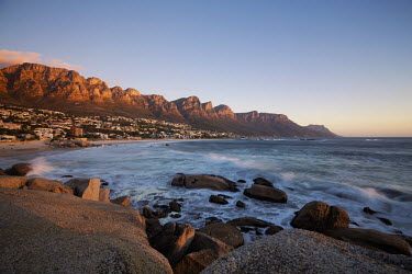 View of Camps Bay at sunset with the view of the Twelve Apostles mountain range - Cape Town, South Africa Aerial,Coastal,Town,Beach,Sand,Mountain,Cliff,Settlement,Civilisation,Ocean,Sea,Bluesky,Rock formation,Sunset