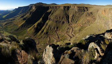 The Sani pass road winds its way up and across the mountain - uKhahlamba Drakensberg Park, South Africa no people,horizontal,day,front view,Africa,African,Southern Africa,scenic,scenery,beauty in nature,natural world,non-urban scene,nature,outdoors,Road,Winding,Cliff,Valley,Landscape